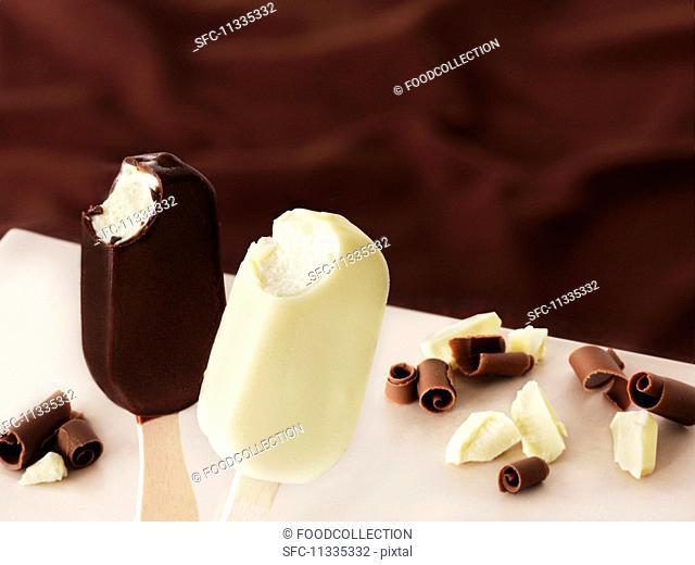 Milk chocolate-covered and white chocolate-covered ice cream sticks