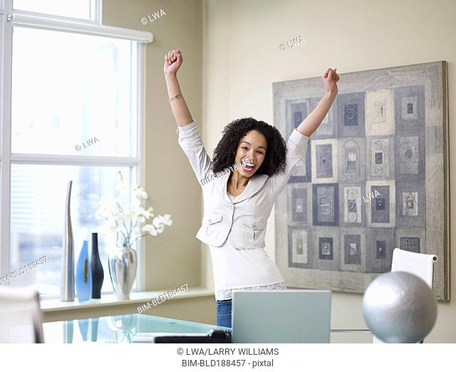 African businesswoman cheering in office