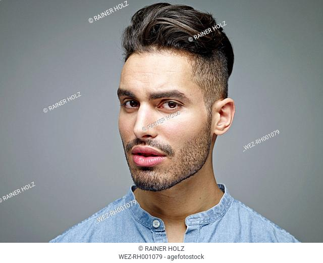 Portrait of sceptical looking young man in front of grey background
