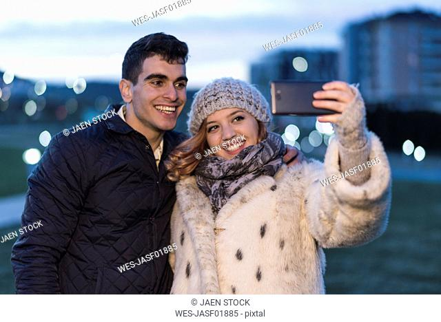 Portrait of happy young couple taking selfie with smartphone in the evening