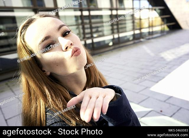 Portrait of young woman with puckering lips. Munich, Germany