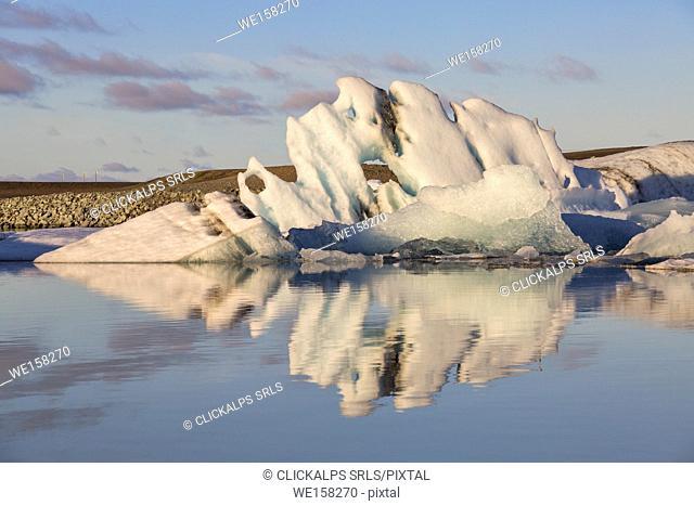 Iceberg reflection in Jokulsarlon Glacier Lagoon during a sunrise, Austurland, Eastern Iceland, Iceland