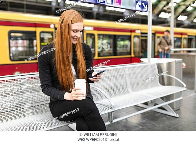 Redheaded young woman with coffee to go waiting at platform using smartphone, Berlin, Germany