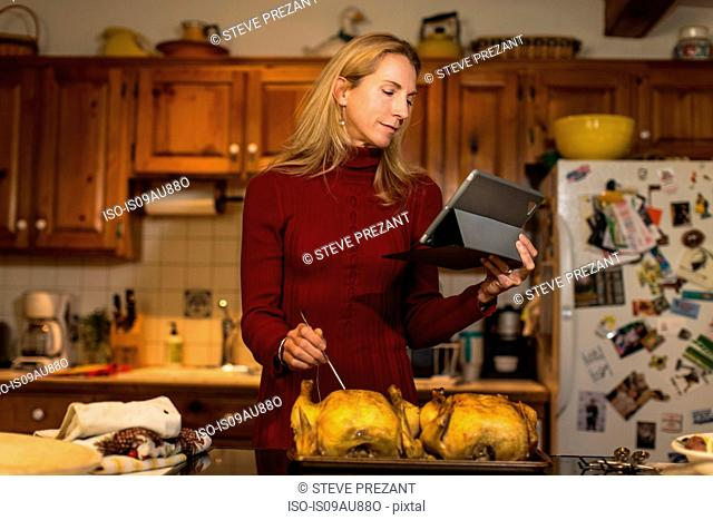 Mature woman using digital tablet to check roast chicken temperature in kitchen