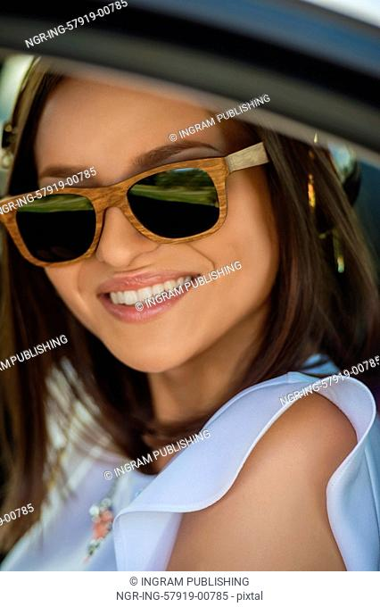 Young pretty girl wearing sunglasses listening music with headphones in car. Summer fun