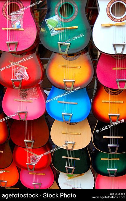 Miniature guitars hang in a vendorâ. . s kiosk at El Pueblo Marketplace in Los Angeles