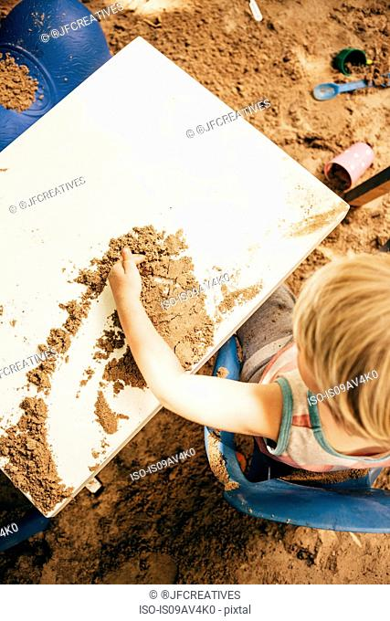 Overhead view of boy sitting at table in sandpit playing with sand