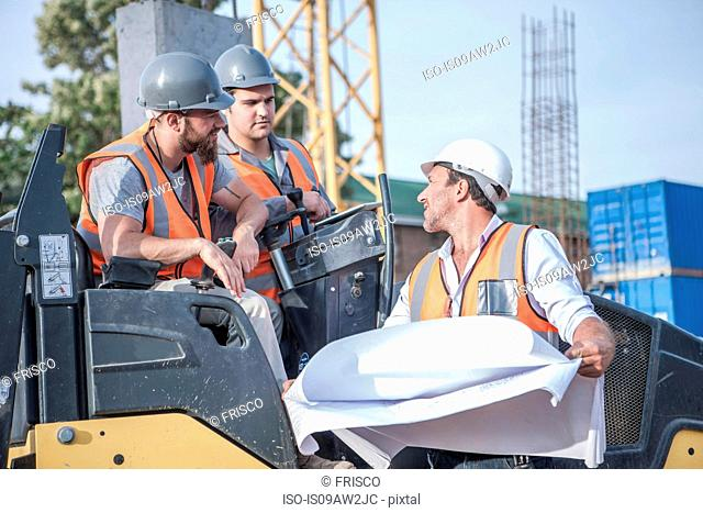 Site manager talking with steamroller drivers about blueprint on construction site