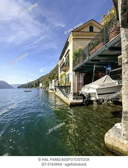 old house with boat suspended in boathouse on lakeside at historical touristic village on Como lake, shot in bright fall light at Moltrasio, Italy
