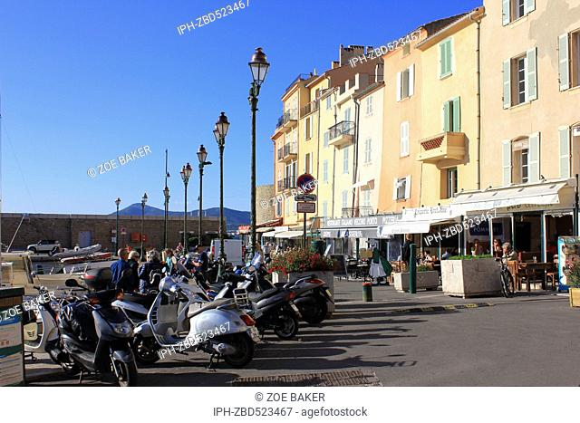 France ,Cote D'Azur, ,St Tropez, Harbourside Cafes and motor scooters. Zoe Baker