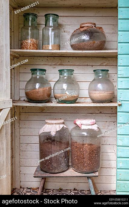 Wooden garden closet with large glass jars filled with diffrent kinds of cereals