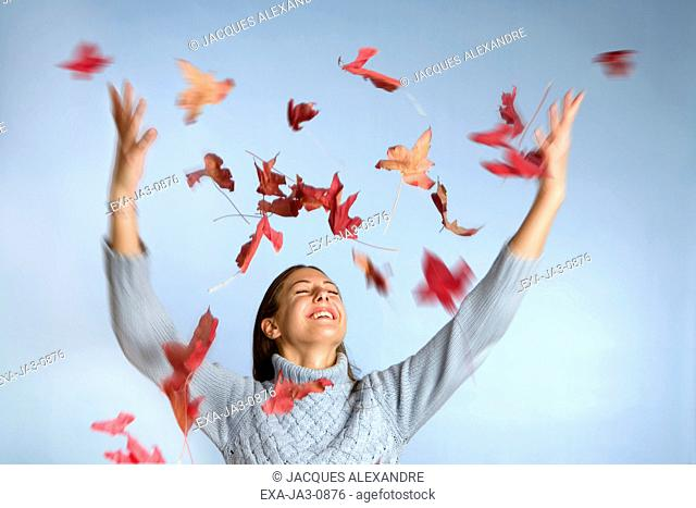 Studio shot of leaves falling on woman with arms raised