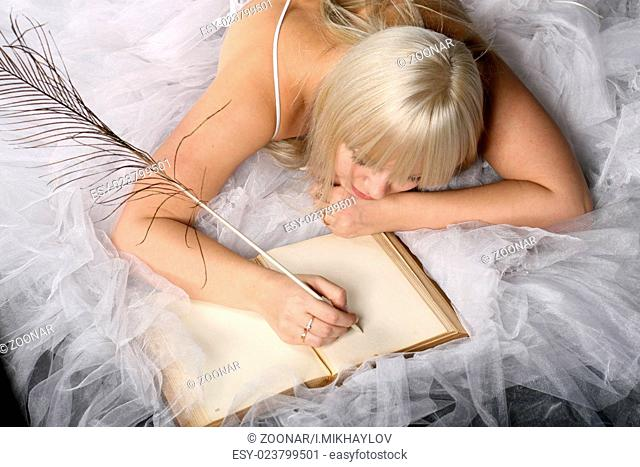 beautiful bride lays on the flor and wrote in old book