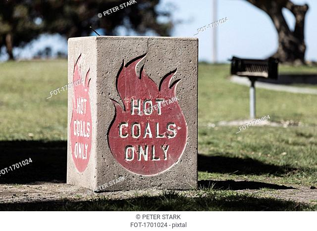 Container for HOT COALS ONLY in park during sunny day