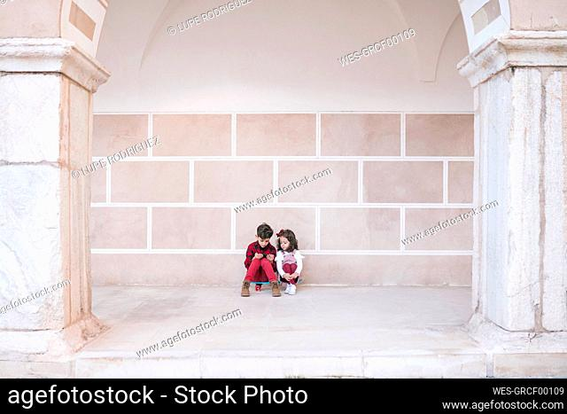Boy and girl sitting on skateboard using smartphone