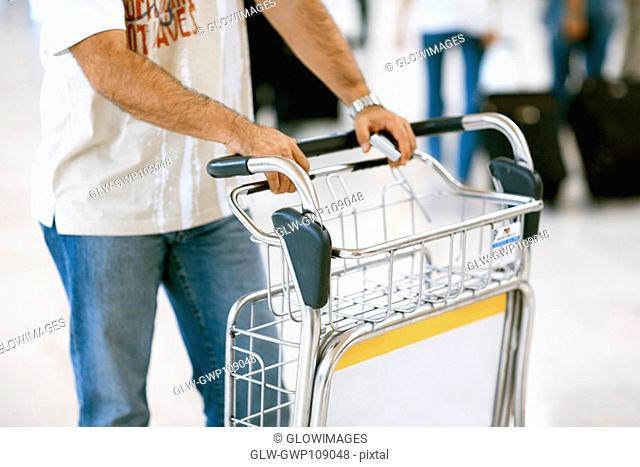 Mid section view of a person standing beside a luggage cart