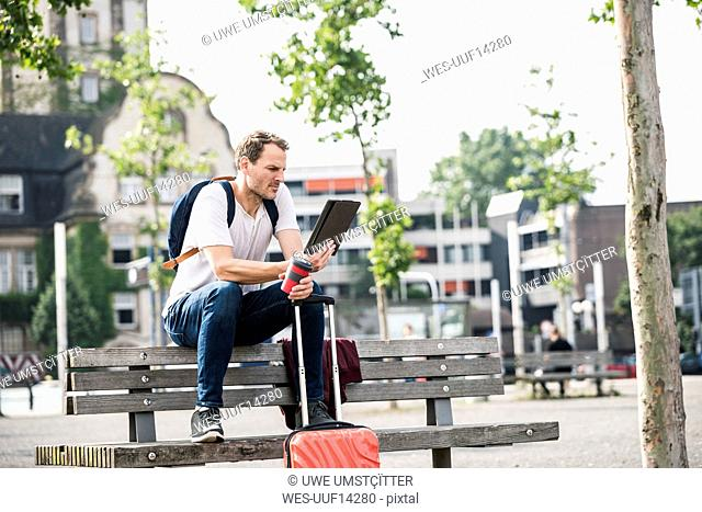 Man with rolling suitcase and takeaway coffee sitting on bench using tablet