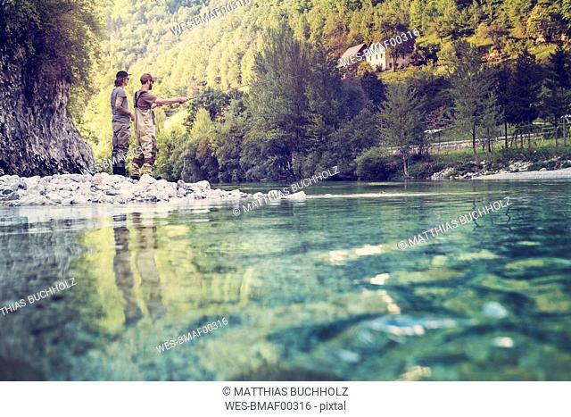Slovenia, two men fly fishing in Soca river