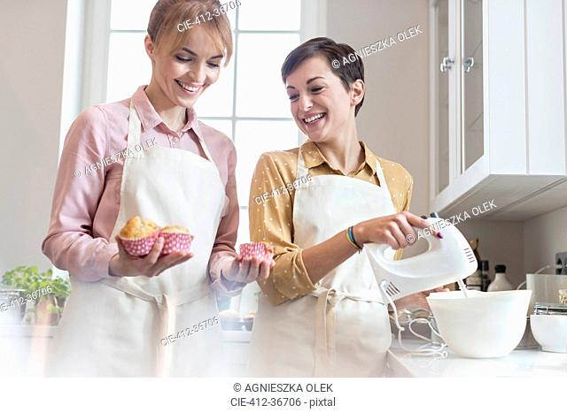Smiling female caterers baking muffins in kitchen