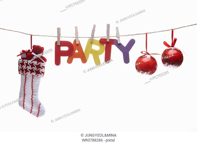 The colorful party word, red Christmas balls, and Christmas stocking hung upon the red string