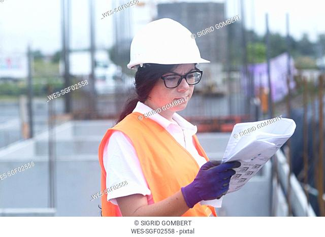 Female construction engineer looking at construction plan