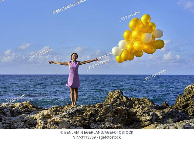 woman at seaside, holding balloons. Freedom, getting away from it all
