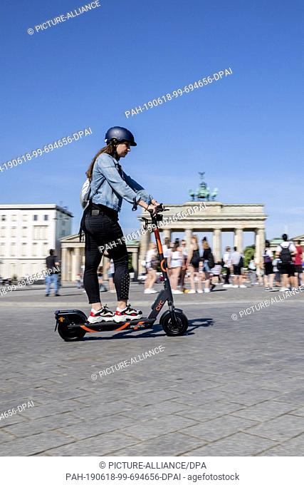 18 June 2019, Berlin: Zeynep Balyali, Marketing Manager at Circ, drives an E-Tretroller at a photo shoot in front of the Brandenburg Gate