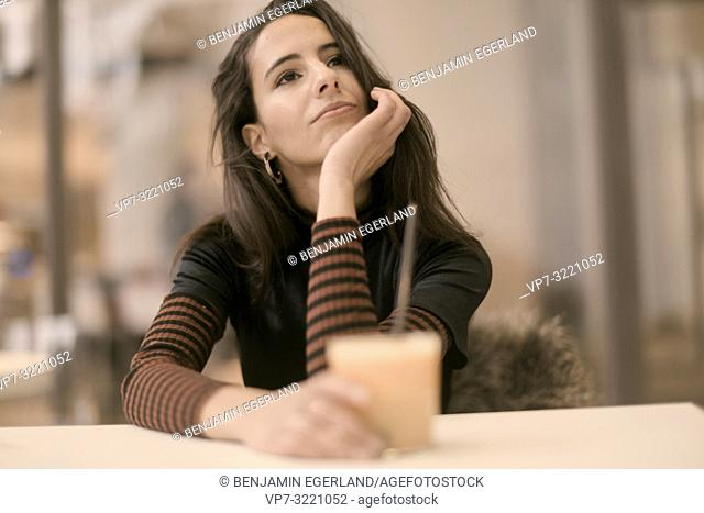 portrait of playful woman holding healthy juice glass while enjoying break at table in café, content, happy, in Munich, Germany