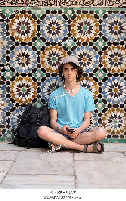 Morocco, Marrakesh, portrait of tourist sitting at tiled wall