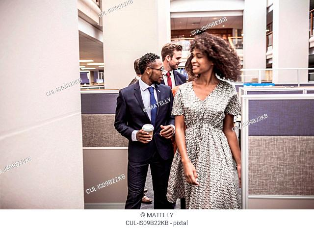 Businesswoman and men walking and talking in office