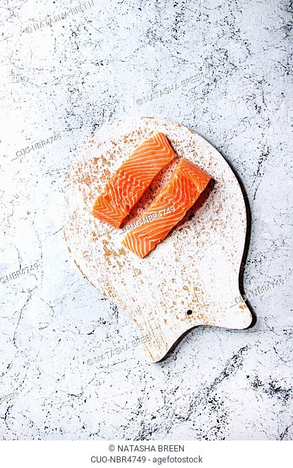 Sliced raw uncooked salmon fillet on wooden chopping board as fish shape with sea salt and pepper over white marble texture background