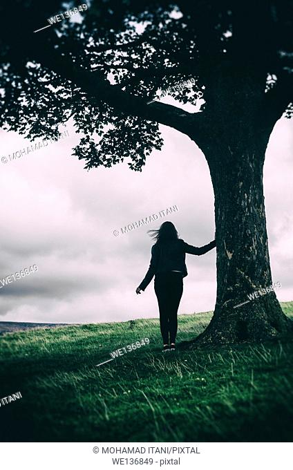 Silhouette of a female figure leaning against a tree in the countryside