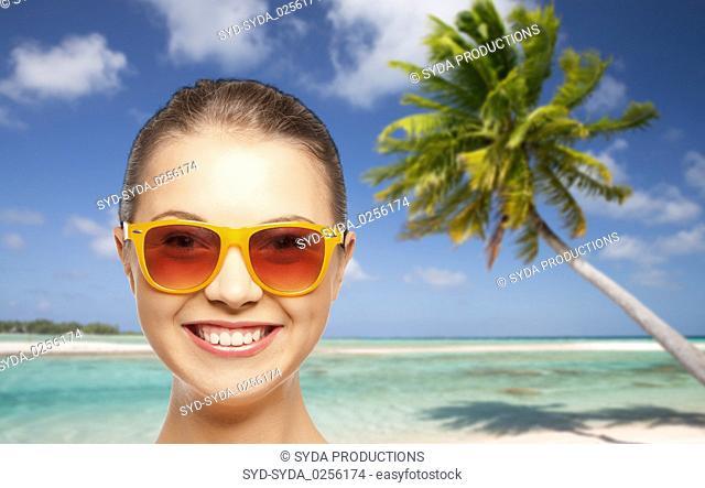 happy woman or teenage girl in sunglasses on beach