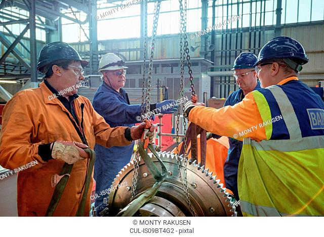 Engineers craning large gear into place in turbine hall of nuclear power station