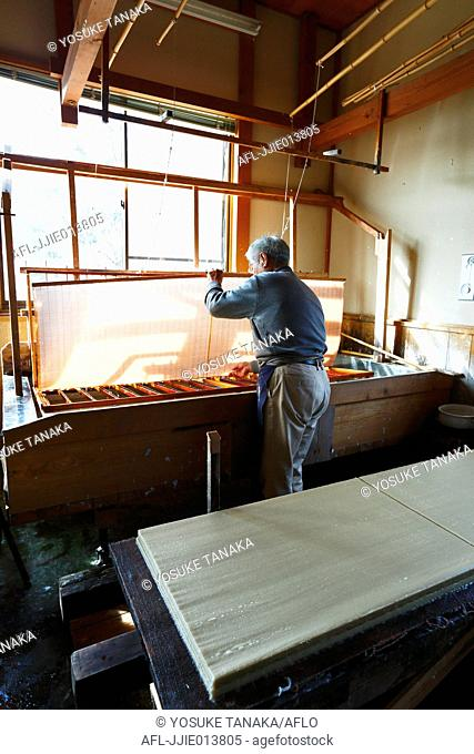 Japanese traditional paper craftsman working in his studio