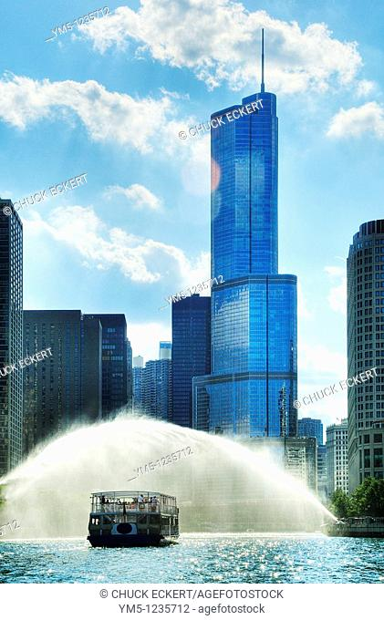 Chicago River architectural cruise boat waiting to pass by Centennial Fountain which erupts every hour during the summer months  Trump Tower is the modern blue...