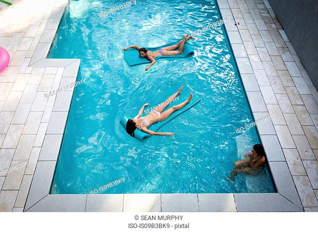 High angle view of two women sunbathing on inflatables in swimming pool, Santa Rosa Beach, Florida, USA
