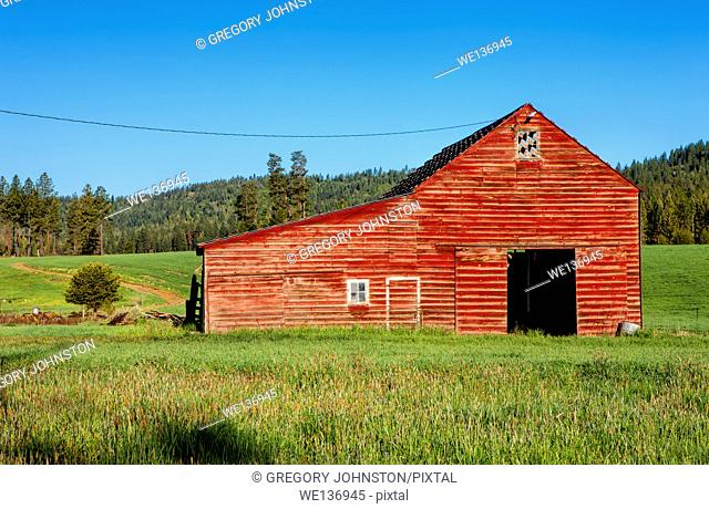 A large red barn in the middle of a green field south of Tensed, Idaho