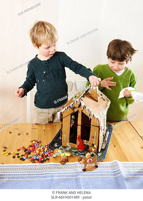 Boys decorating gingerbread house