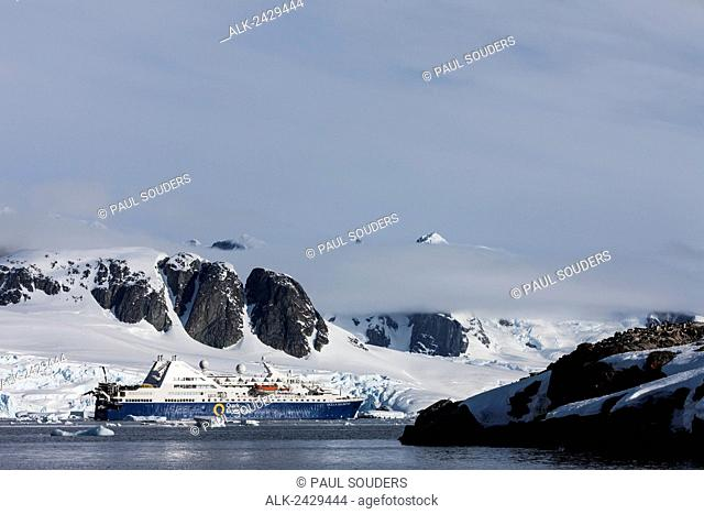 Antarctica, Petermann Island, Cruise ship anchored near glacier-covered mountains near Lemaire Channel on sunny evening