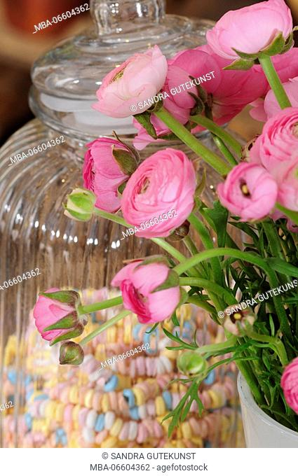 bunch of buttercups and candy necklaces in storage jar, Ranunculus asiaticus, close-up