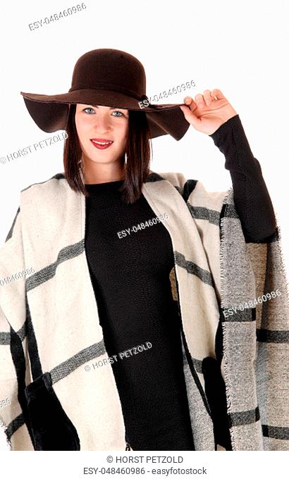 A beautiful woman standing is a black dress with a big poncho over .her shoulder, wearing a hat, smiling, isolated for white background