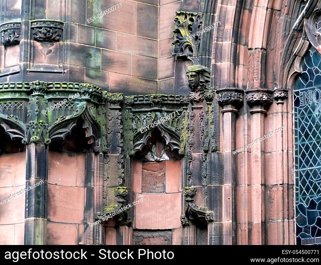 details of ornately carved medieval stonework with niches and faces on the facade of chester cathedral