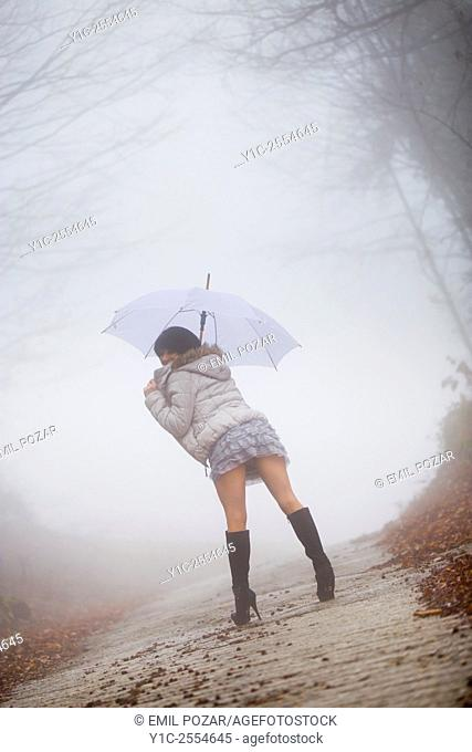 Stock Photo - Young woman under umbrella lost in fog