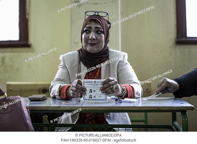 A volunteer holds a ballot with the picture of Egyptian president Abdel Fattah al-Sisi and his opponent Moussa Mostafa Moussa in a polling station on the first...