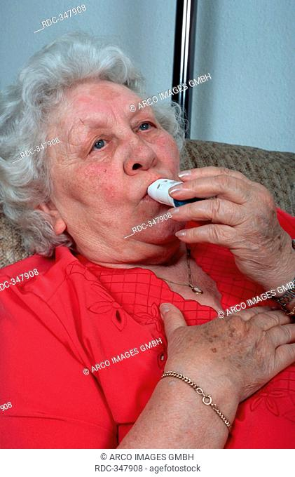 Elderly woman, sufferer from asthma, asthma attack, using aspirator, asthma inhaler, ventilatory support, respiratory diseases, inhaling