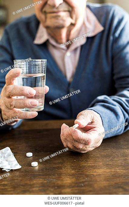 Senior man taking medicine, close-up