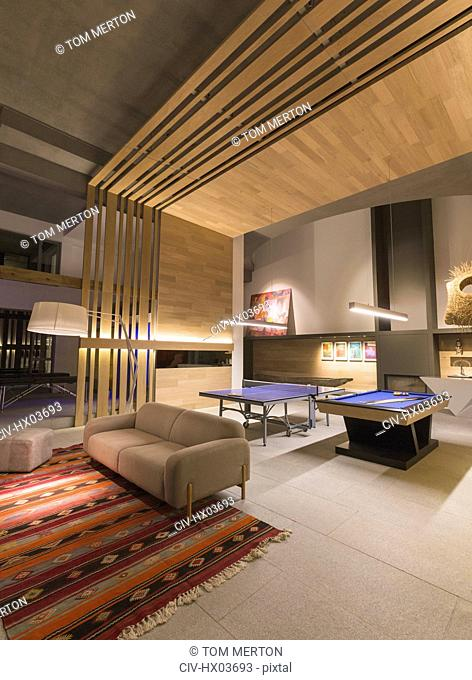 Illuminated modern, luxury home showcase interior game room with pool table and ping pong table