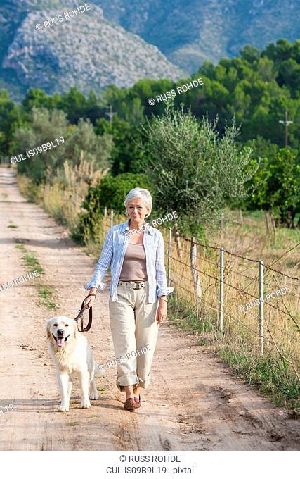 Portrait of senior woman walking pet dog