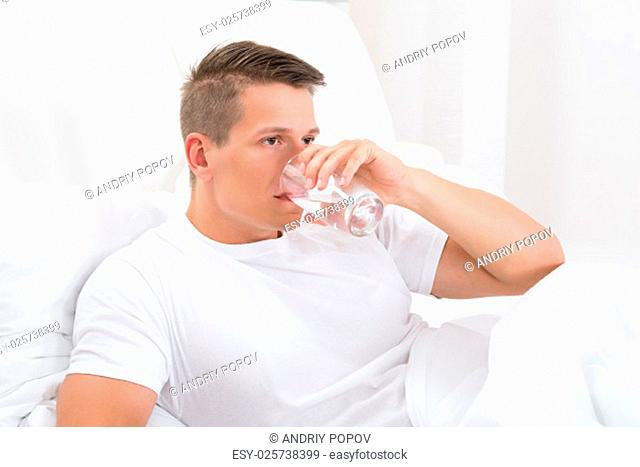 Young Man Sitting In Bed Drinking Water